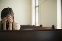 Woman with her face in her hands, praying in a church pew.