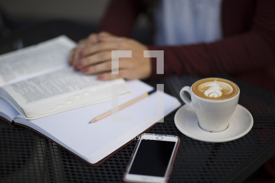 a young woman reading a Bible and journaling at a table with a mug of coffee and cellphone