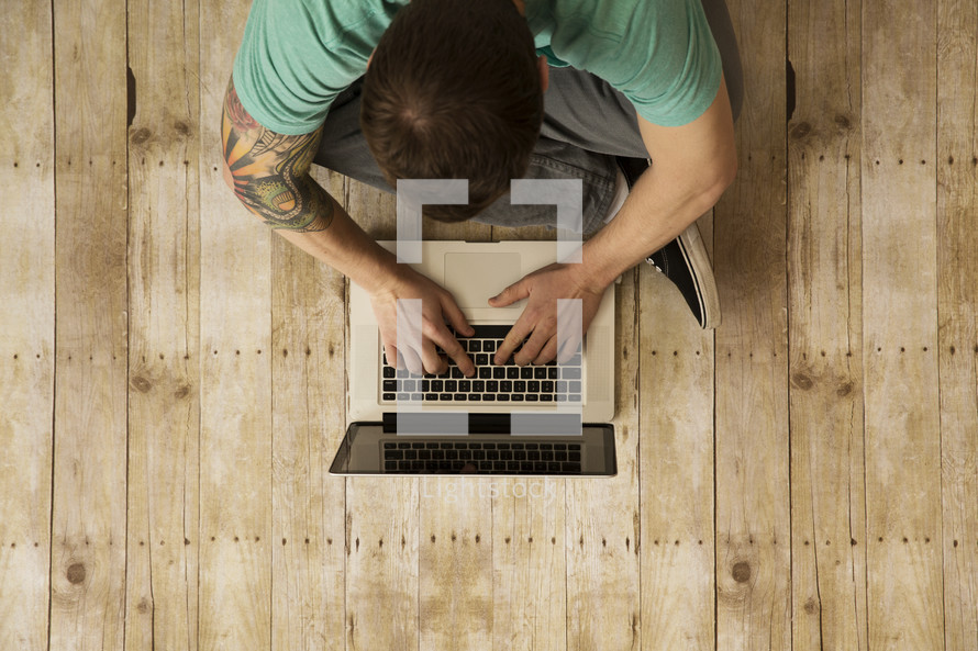 an above view of a man sitting on a wood floor typing on a laptop computer.