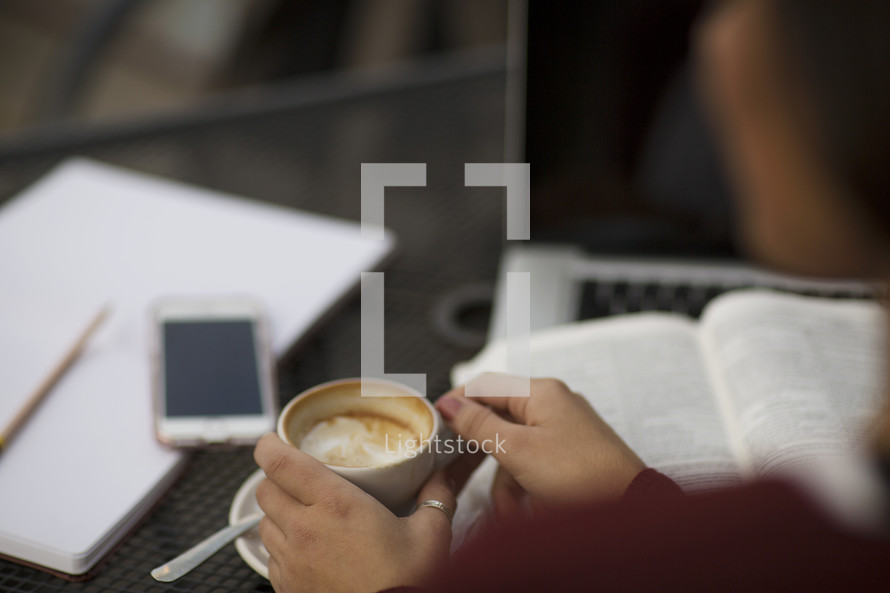 a young woman reading a Bible and writing in a journal at a table with a coffee mug and cellphone