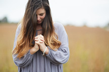 a woman with head bowed and praying hands standing in a field praying