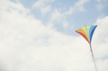 a rainbow colored kite in the sky.
