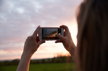 a woman taking a picture of the sky at sunset with her smartphone