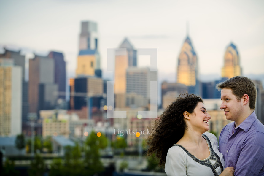 couple embracing - city skyline  background