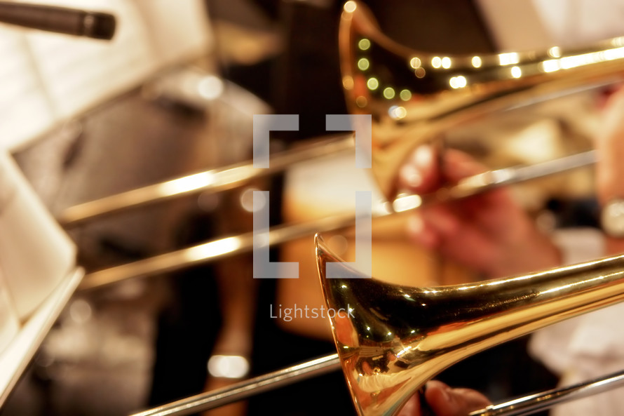 Close-up of trombones playing in a church worship band or church orchestra - focus point on foreground trombone.