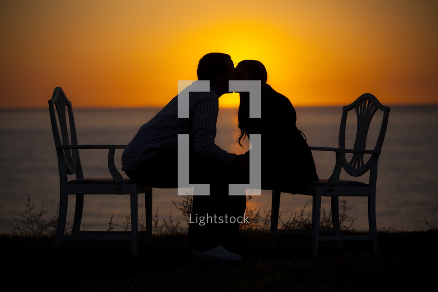 Silhouettes of a man and woman kissing at sunset
