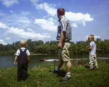 father with his two sons standing near a lake