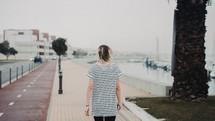 woman walking along a harbor