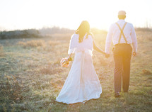bride and groom walking outdoors holding hands