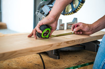 Man holding a measuring tape over a piece of wood under a chop saw.