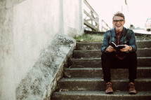 a young man sitting on steps holding a Bible
