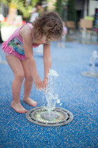 toddler girl in a bathing suit playing in a fountain at a splash pad