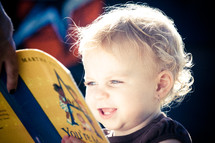 toddler girl reading a book about music - singing