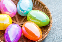 Plastic Easter eggs sitting in a circular brown basket on a textured background