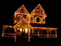 A Christmas Ginger bread house decorated with Christmas lights adorns the night sky at Christmas time.