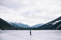 a woman walking across a frozen lake in winter in Canada