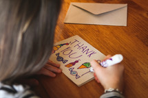 a child drawing a thank you card