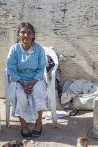 old woman sitting in plastic chair