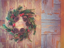 Christmas wreath decoration on colorful painted farmhouse door