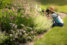 a woman taking pictures of flowers