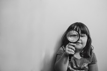 a girl child looking through a magnifying glass