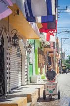 man pushing an ice cream cart down a cobble stone street