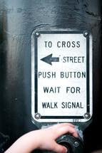 A little boys hand pressing the cross street button at a crosswalk.