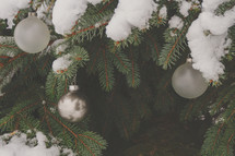 Snowy Christmas pine tree in nature with ornaments