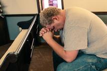 a man praying alone in a church