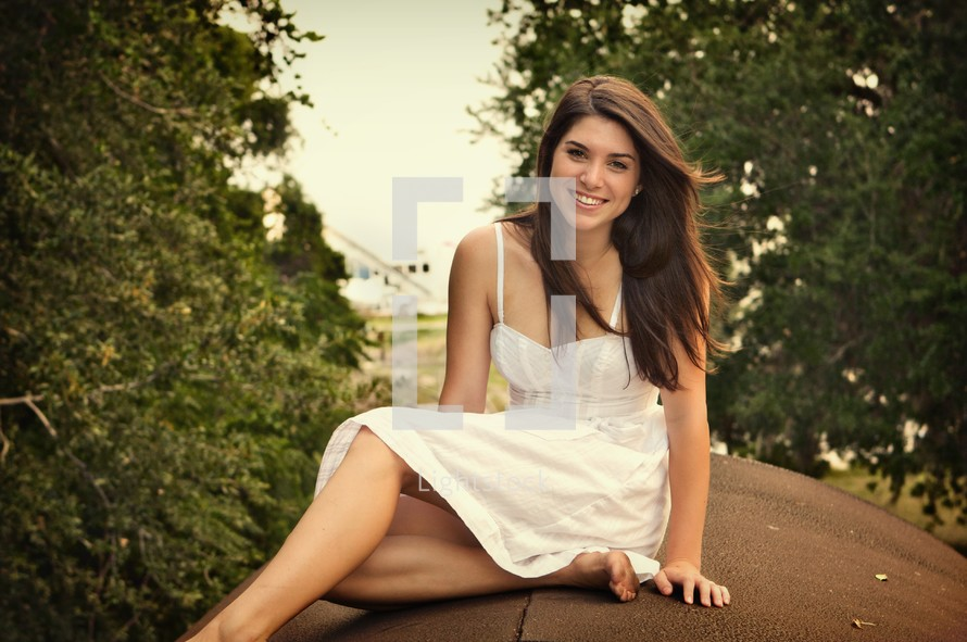 teen in a white dress siting outside