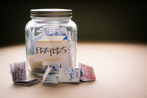 "A glass jar labeled ""prayers"" full of handwritten notes."