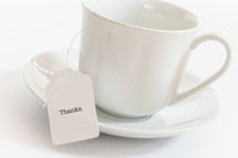 tea cup with a tea bag with the word thanks