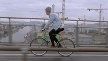 a man riding a bicycle across a city bridge