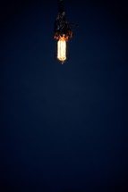 An old fashioned lightbulb shines in the dark