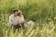 Happy couple sitting in grass field