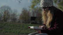 teen girl reading a Bible outdoors