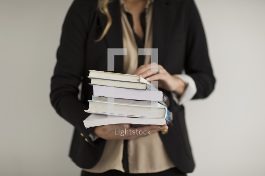 a student holding a stack of books