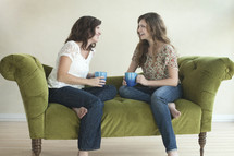 two friends drinking coffee and talking on a couch