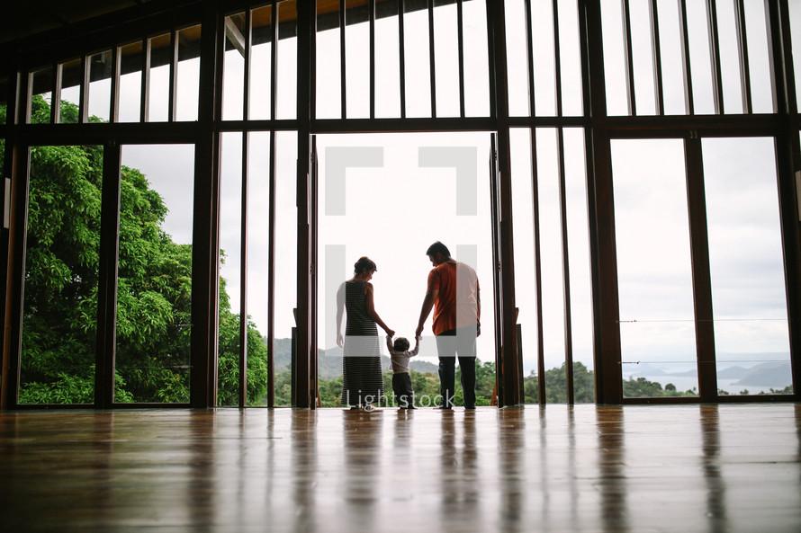 Family holding hands walking towards the balcony
