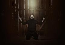 a man kneeling in prayer in a barn