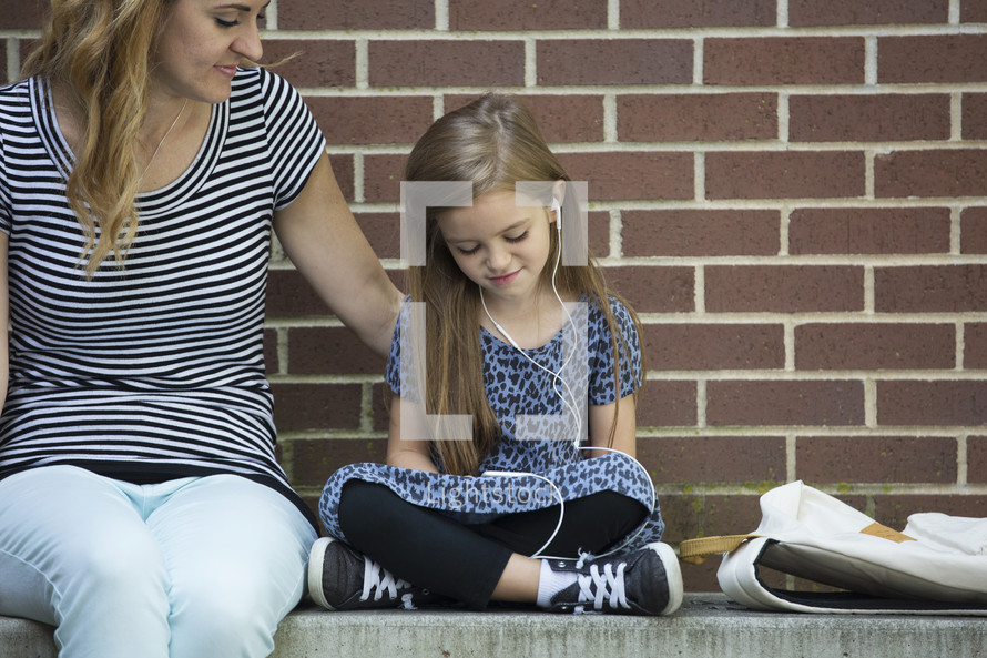a mother and child on a bench reading a book while waiting for school to start
