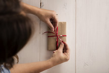 A ribbon being tied on a wrapped gift.