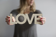 a woman holding a sign of the word love