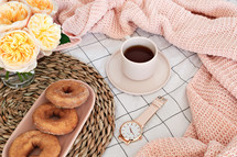 vase, donuts, mat, scarf, watch, and coffee