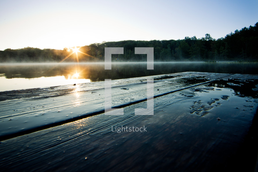 The sun rises over the trees and reflects off the dock.