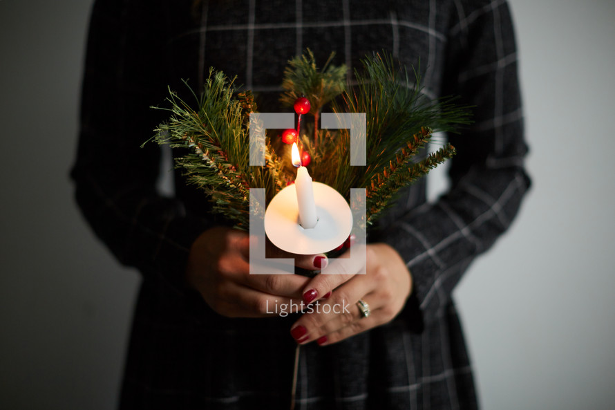 a woman holding a candle and Christmas greenery