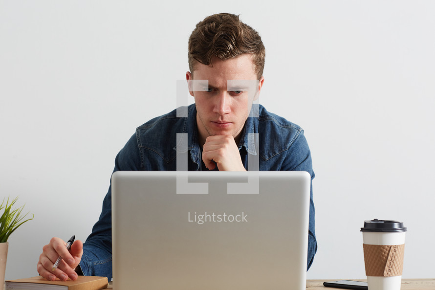 a man thinking sitting behind a computer
