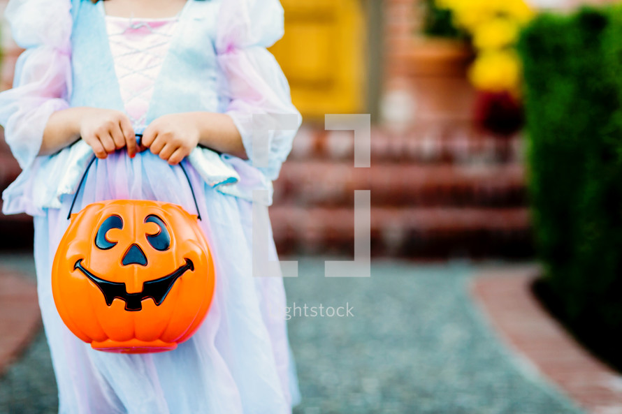 a child in a princess costume trick or treating