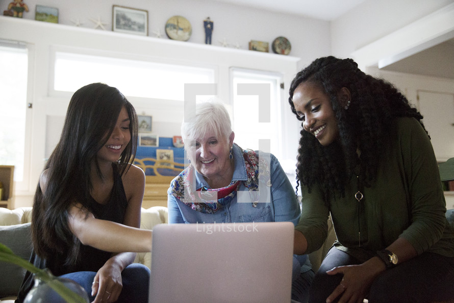 women working together looking at a laptop computer screen