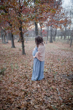 pregnant woman holding her belly outdoors in fall